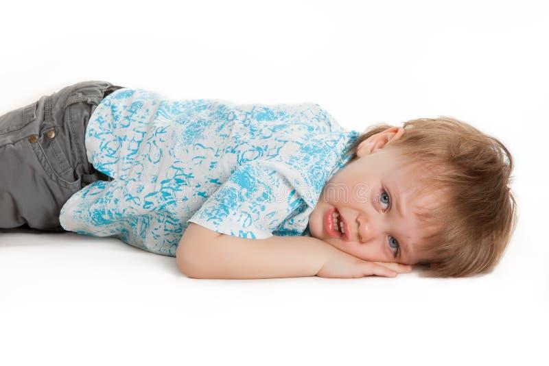 Giovane ragazzino che si trova sul pavimento su bianco immagini stock libere da diritti