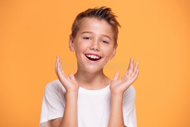 Giovane ragazzino emozionale sul fondo arancio dello studio fotografia stock