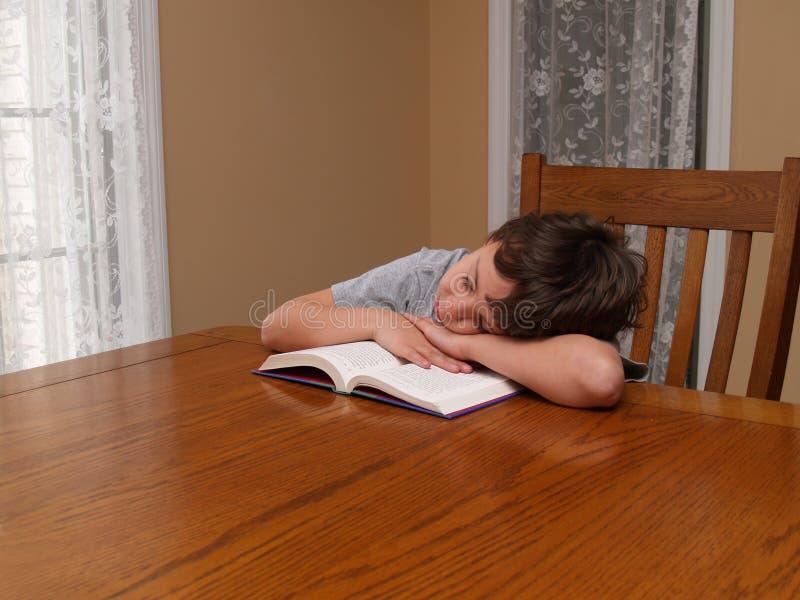 Giovane ragazzo addormentato mentre leggendo immagine stock libera da diritti