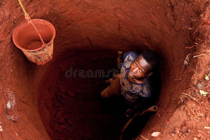 Giovane ragazzo africano dentro il pozzo d'acqua in Africa durante lo sguardo di scavatura in camera visto da sopra, con il secch fotografia stock