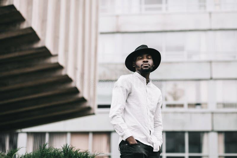 Giovane ragazzo afroamericano bello in cappello alla moda dei pantaloni a vita bassa immagine stock