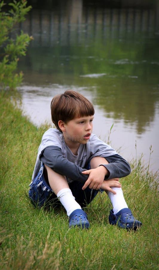 Giovane ragazzo al fiume immagine stock