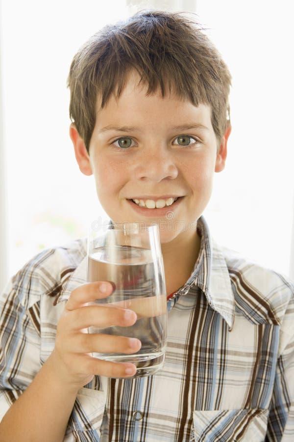 Giovane ragazzo all'interno sorridere dell'acqua potabile fotografia stock