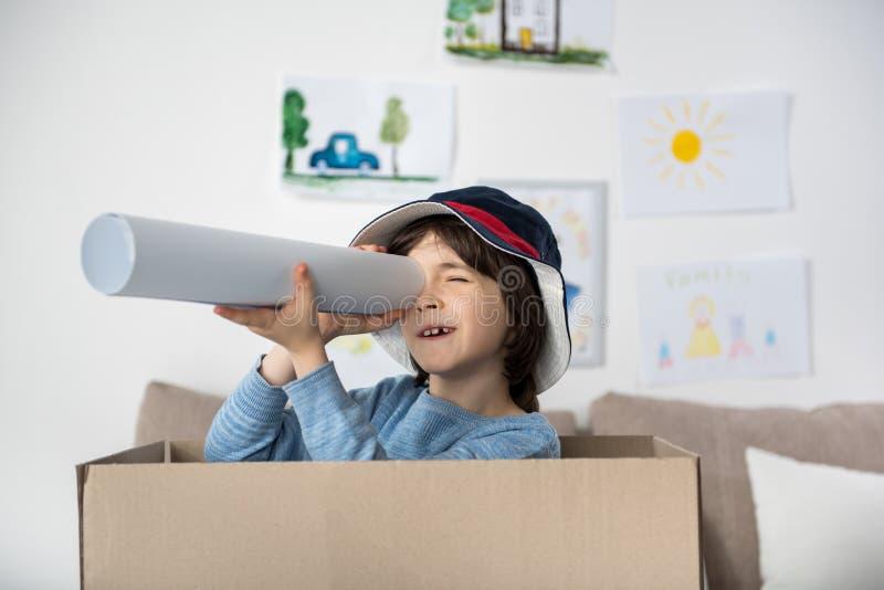 Giovane ragazzo allegro con il telescopio immaginario immagine stock libera da diritti