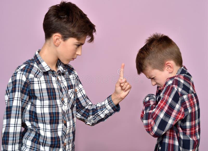 Giovane ragazzo arrabbiato che rimprovera un fratello fotografie stock libere da diritti