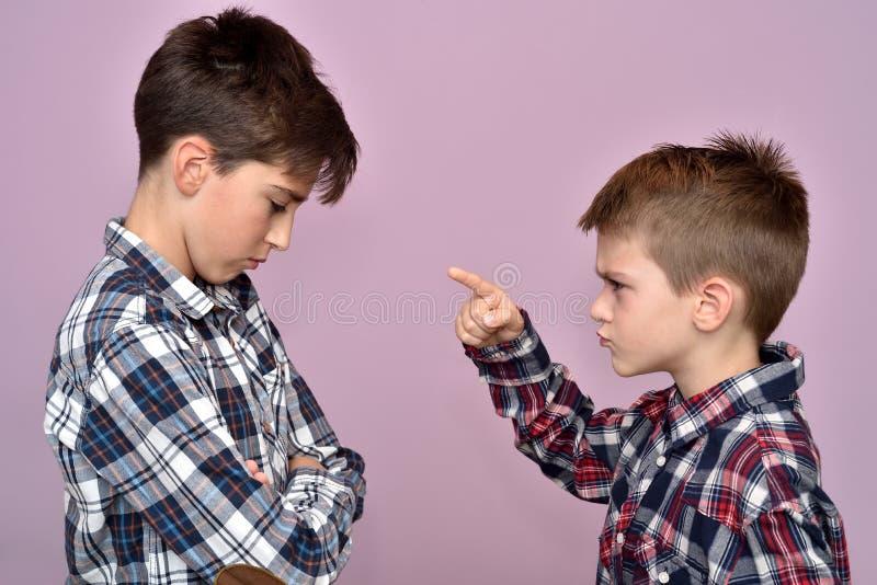 Giovane ragazzo arrabbiato che rimprovera un fratello fotografia stock