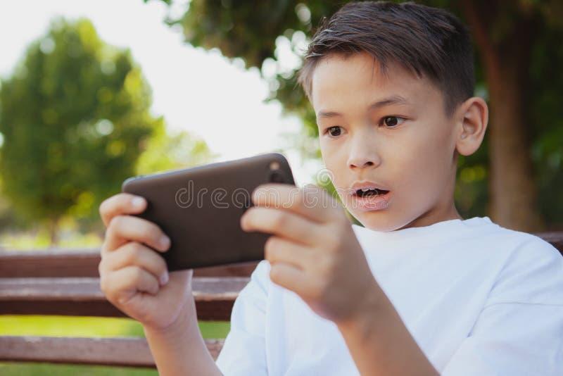 Giovane ragazzo asiatico che gioca sul suo Smart Phone al parco fotografia stock