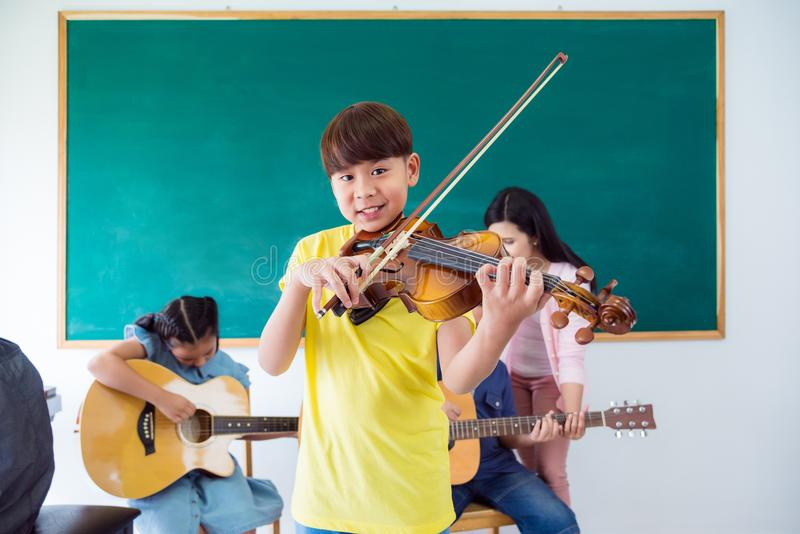 Giovane ragazzo asiatico che sorride mentre giocando violino nella classe di musica alla s immagine stock libera da diritti