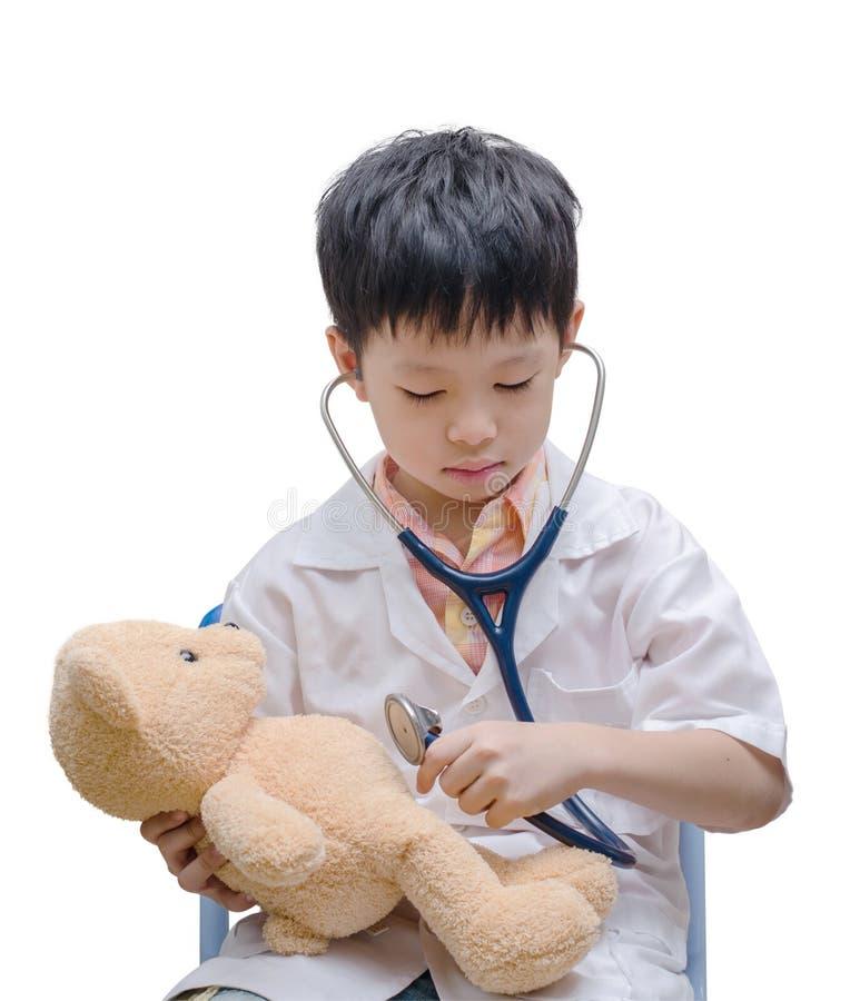 Giovane ragazzo asiatico di medico che gioca e che cura il giocattolo dell'orso immagine stock
