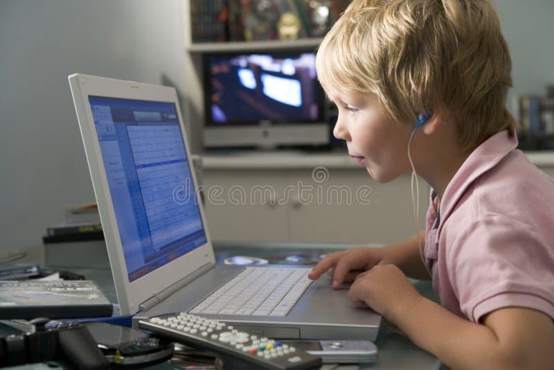Giovane ragazzo in camera da letto per mezzo del computer portatile ed ascoltando fotografia stock libera da diritti