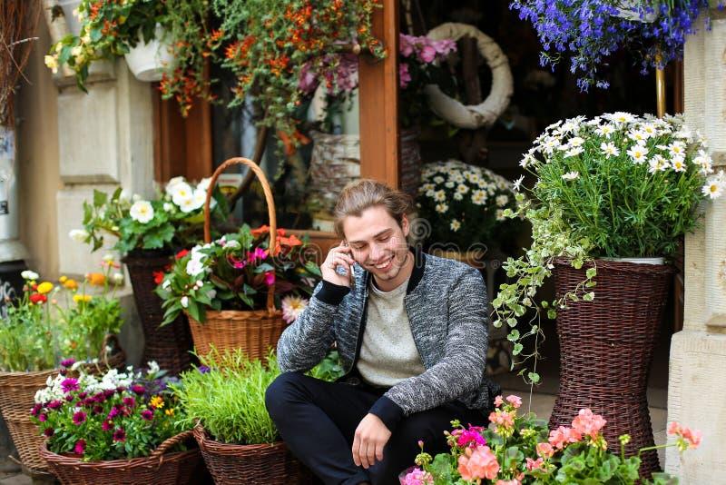 Giovane ragazzo caucasico che parla con uno smartphone e siede in un negozio di fiori vicino ai bouquet nei cestini fotografia stock libera da diritti