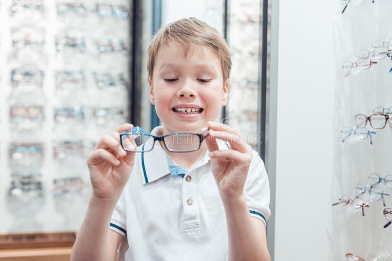 Giovane ragazzo che è molto soddisfatto dei suoi nuovi occhiali nel deposito fotografia stock libera da diritti