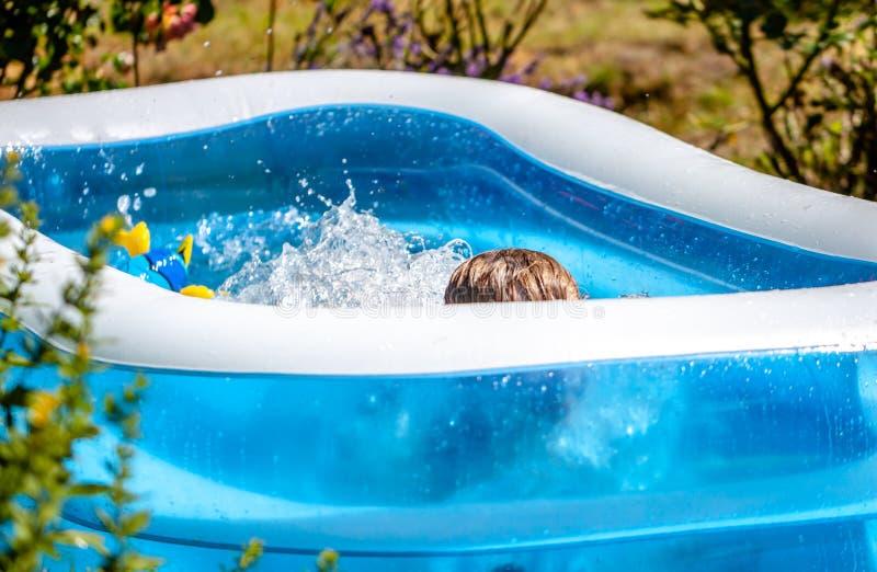 Giovane ragazzo che annega nella piscina di estate fotografie stock