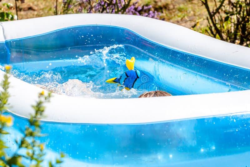 Giovane ragazzo che annega nella piscina di estate fotografia stock