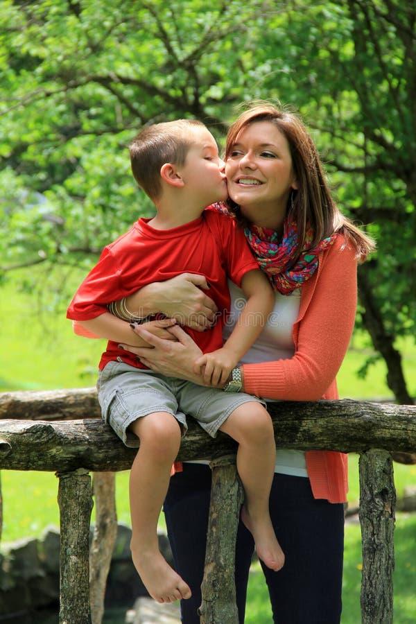 Giovane ragazzo che bacia mamma felice fotografia stock libera da diritti