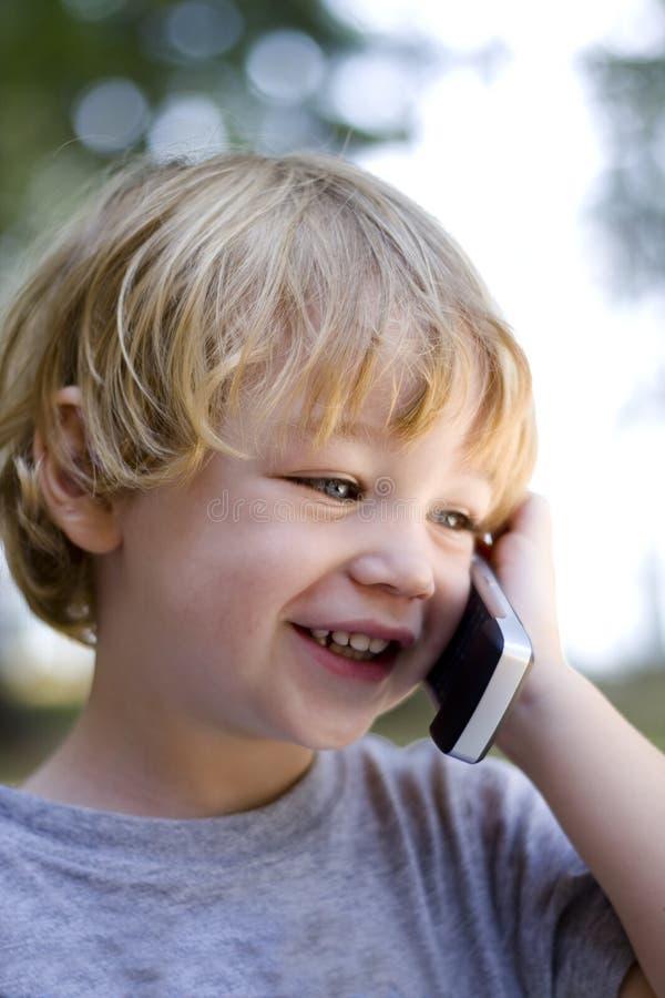 Giovane ragazzo che comunica sul telefono delle cellule immagini stock