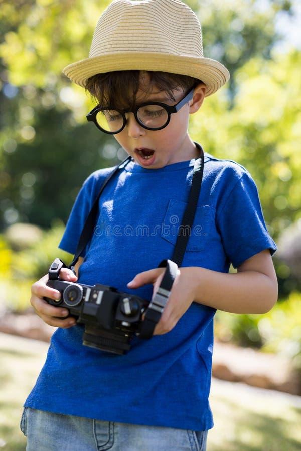 Giovane ragazzo che controlla una fotografia in camera fotografia stock libera da diritti