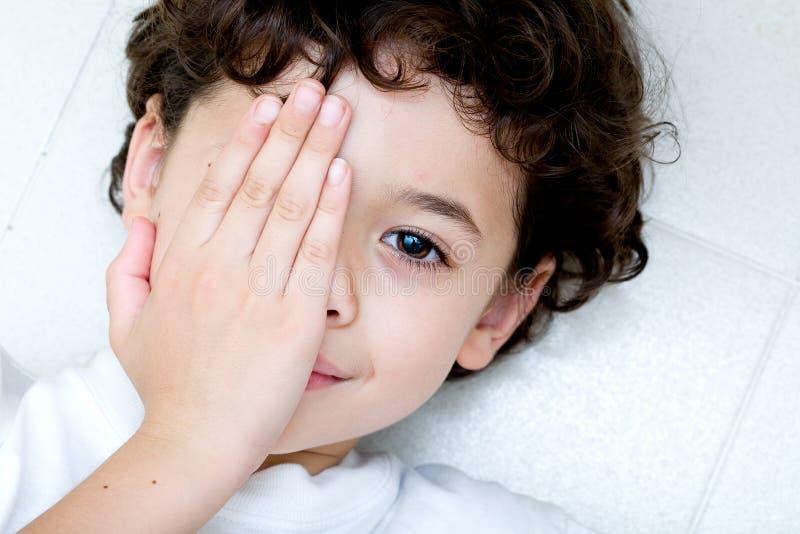 Giovane ragazzo che copre un occhio. fotografia stock