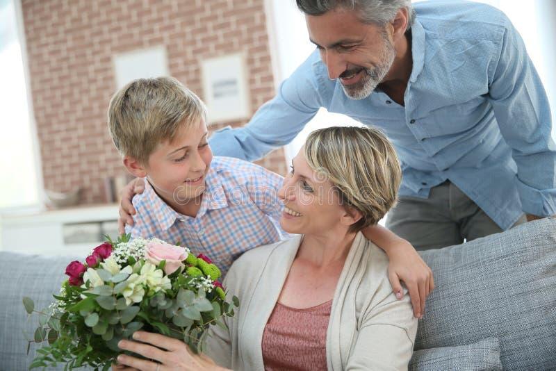 Giovane ragazzo che dà i fiori a sua madre fotografie stock libere da diritti