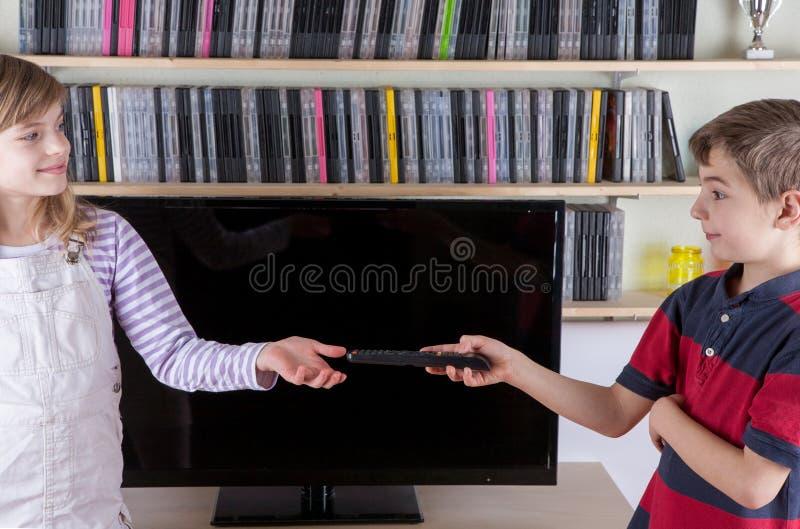 Giovane ragazzo che dà il telecomando a sua sorella davanti a Th fotografia stock