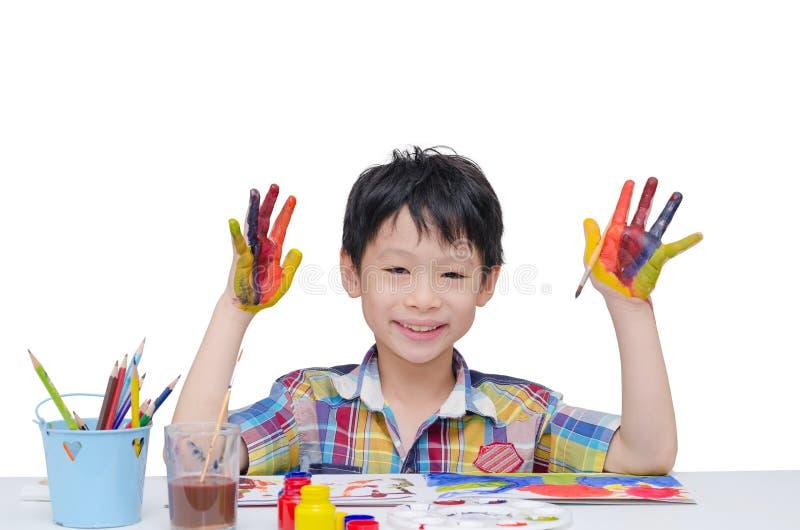 Giovane ragazzo che dipinge le sue mani fotografia stock libera da diritti