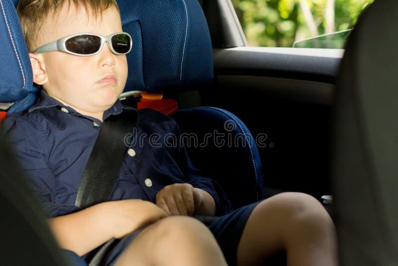 Giovane ragazzo che dorme nella sede di automobile del bambino immagini stock