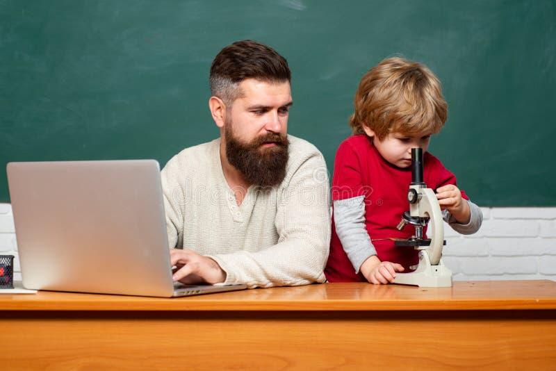 Giovane ragazzo che fa il suo compito della scuola con suo padre Di nuovo al banco Istruzione ed imparare concetto della gente -  fotografie stock