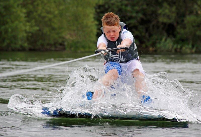 Giovane ragazzo che fa wakeboarding/che pratica il surfing fotografia stock libera da diritti