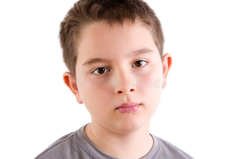 Giovane ragazzo che fissa alla macchina fotografica con l'espressione in bianco immagini stock