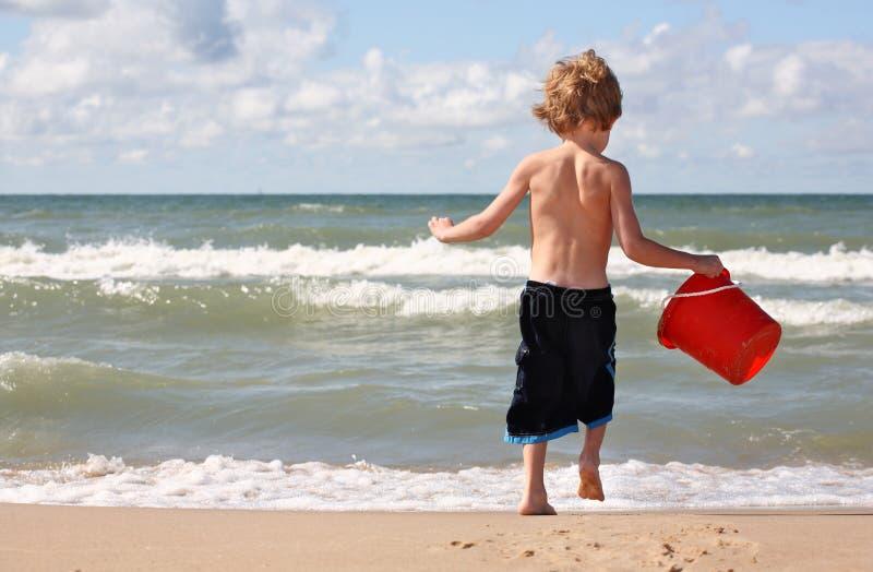 Giovane ragazzo che gioca alla spiaggia fotografie stock libere da diritti