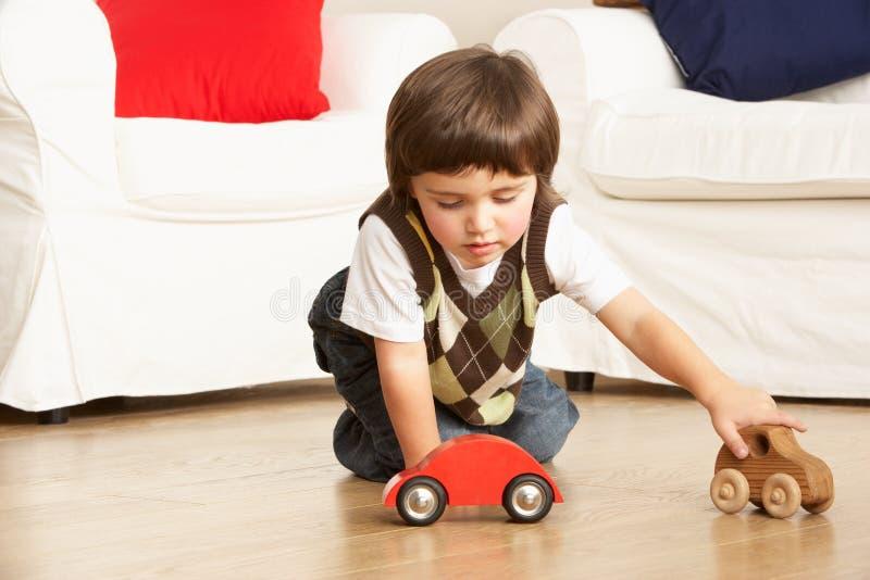 Giovane ragazzo che gioca con le automobili del giocattolo nel paese fotografia stock libera da diritti