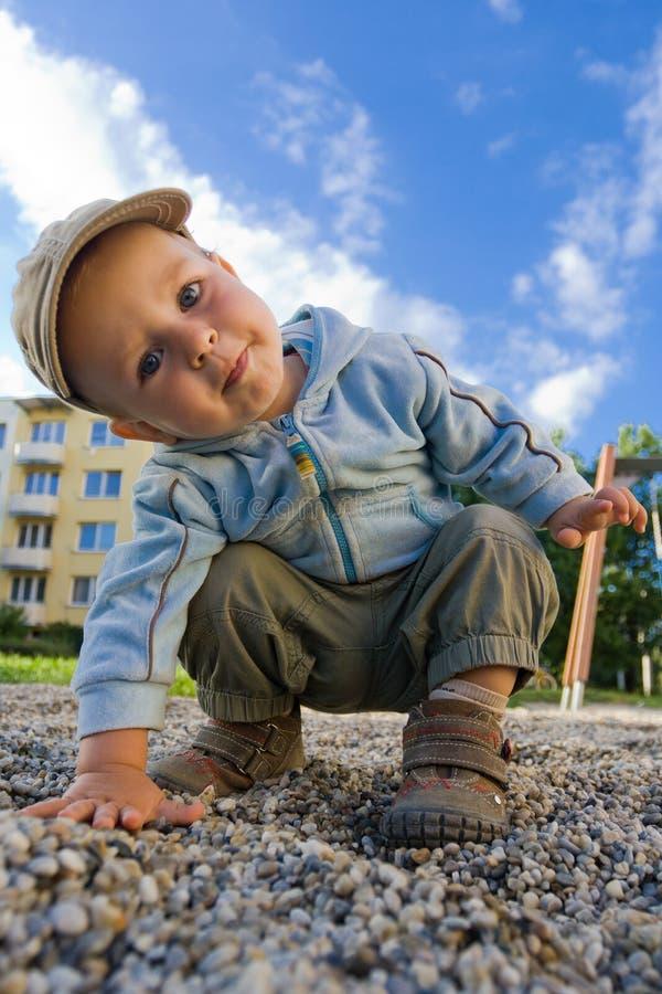 Giovane ragazzo che gioca sul campo da giuoco immagini stock