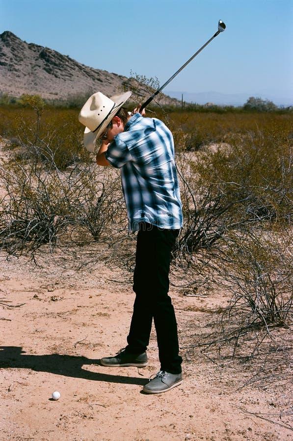Giovane ragazzo che golfing nel deserto fotografia stock libera da diritti