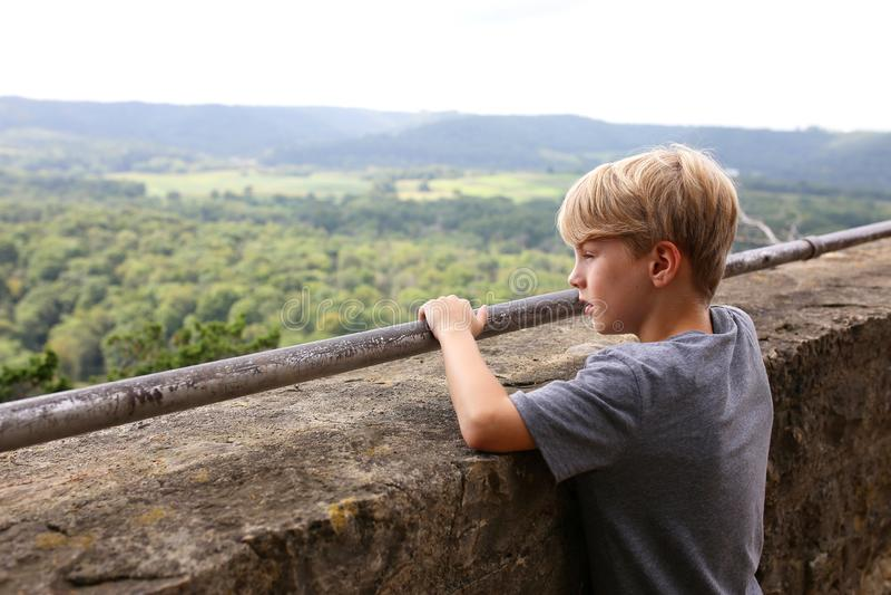 Giovane ragazzo che guarda fuori sopra il bordo di Cliff Viewing scenico turistico immagini stock