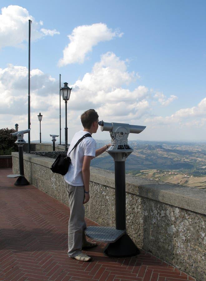 Giovane ragazzo che guarda tramite un telescopio immagini stock libere da diritti