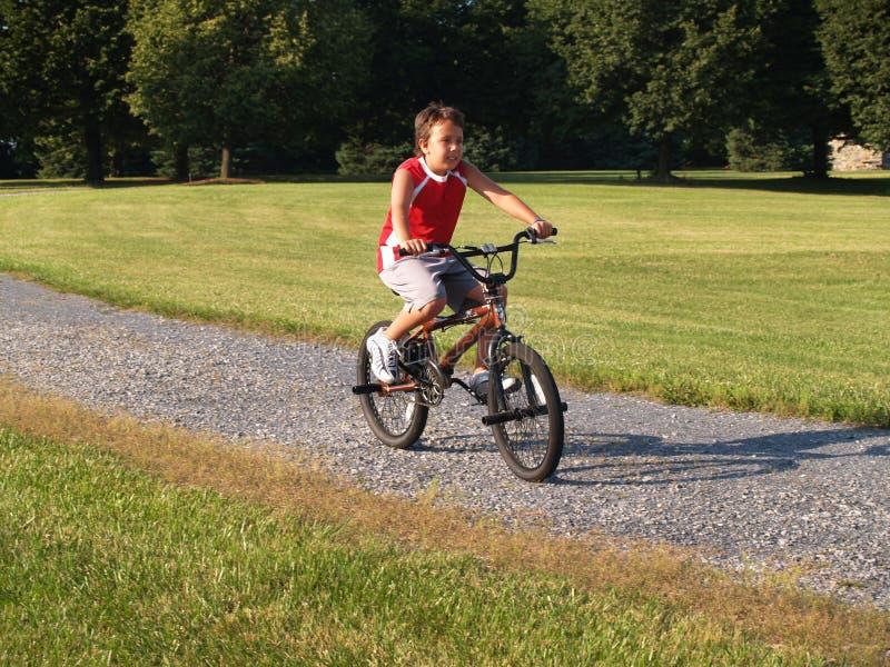 Giovane ragazzo che guida una bici immagine stock