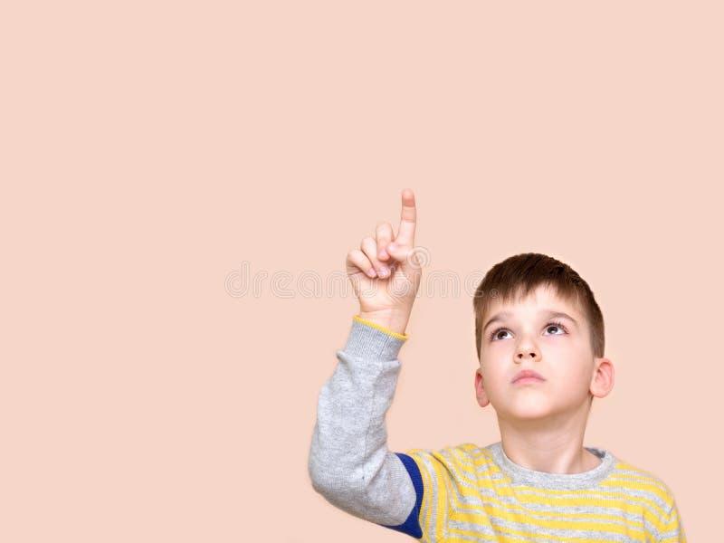 Giovane ragazzo che indica su con il suo dito indice immagine stock libera da diritti