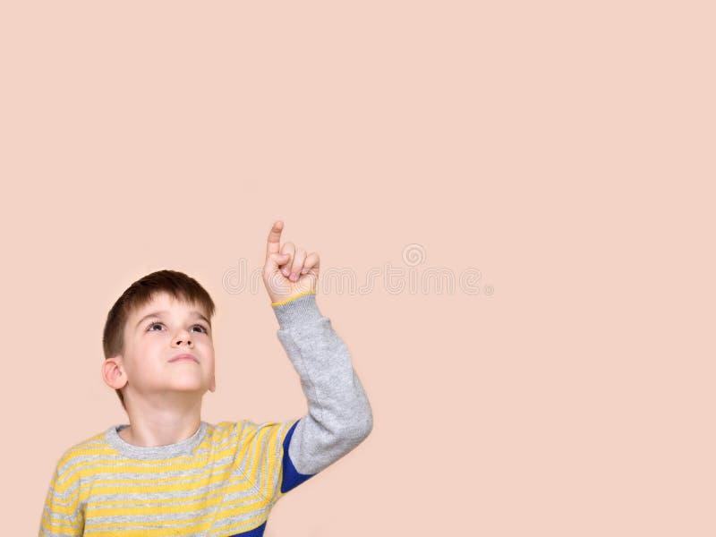 Giovane ragazzo che indica su con il suo dito indice fotografia stock libera da diritti