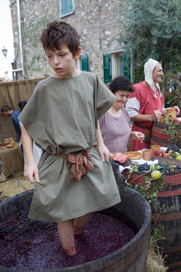 Giovane ragazzo che indossa l'uva medievale d'annata battere i piedi dei vestiti nel tino di legno fotografia stock libera da diritti