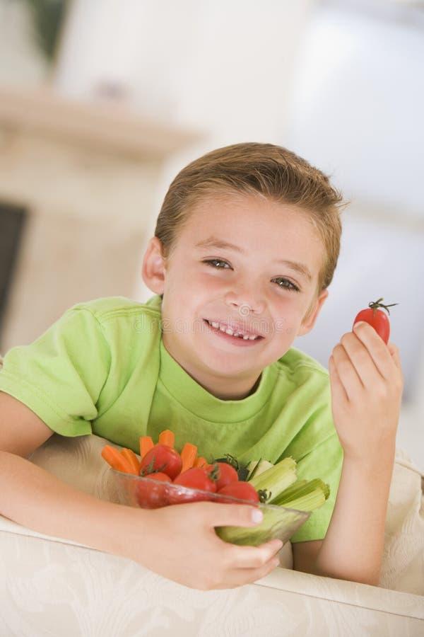 Giovane ragazzo che mangia ciotola di verdure in salone fotografia stock