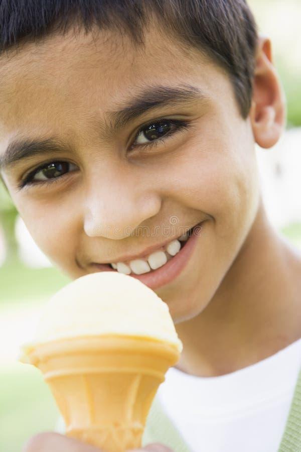 Giovane ragazzo che mangia il cono di gelato fotografie stock libere da diritti