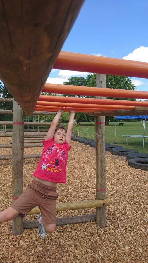 Giovane ragazzo che oscilla sulle barre di scalata di scimmia della struttura fotografie stock