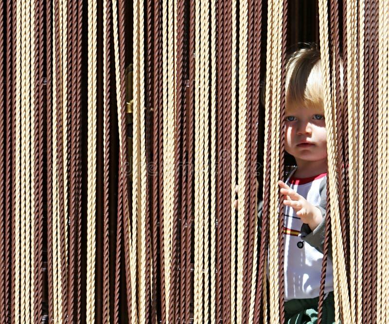 Giovane ragazzo che osserva fuori da dietro la tenda immagini stock