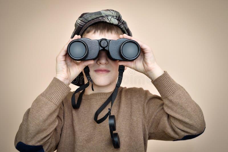 Giovane ragazzo che osserva tramite il binocolo immagini stock libere da diritti