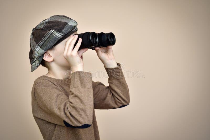 Giovane ragazzo che osserva tramite il binocolo immagine stock
