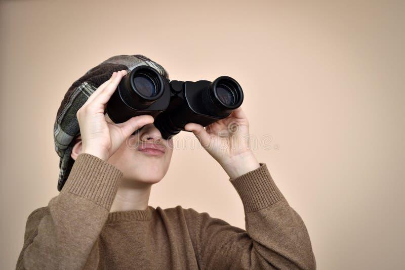 Giovane ragazzo che osserva tramite il binocolo fotografie stock libere da diritti