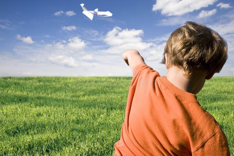 Giovane ragazzo che pilota un aereo di carta immagine stock libera da diritti