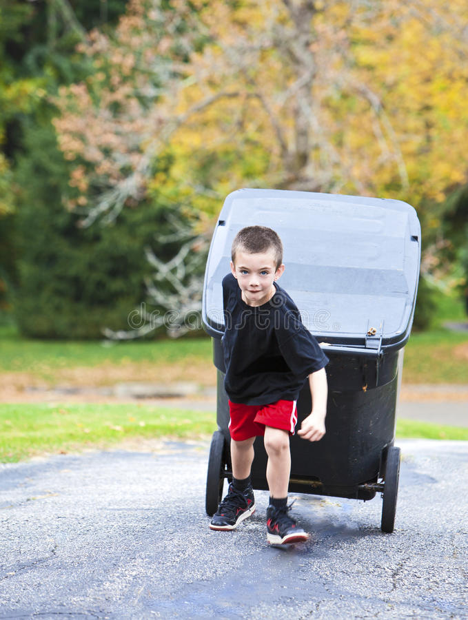 Giovane ragazzo che porta pattumiera su fotografia stock