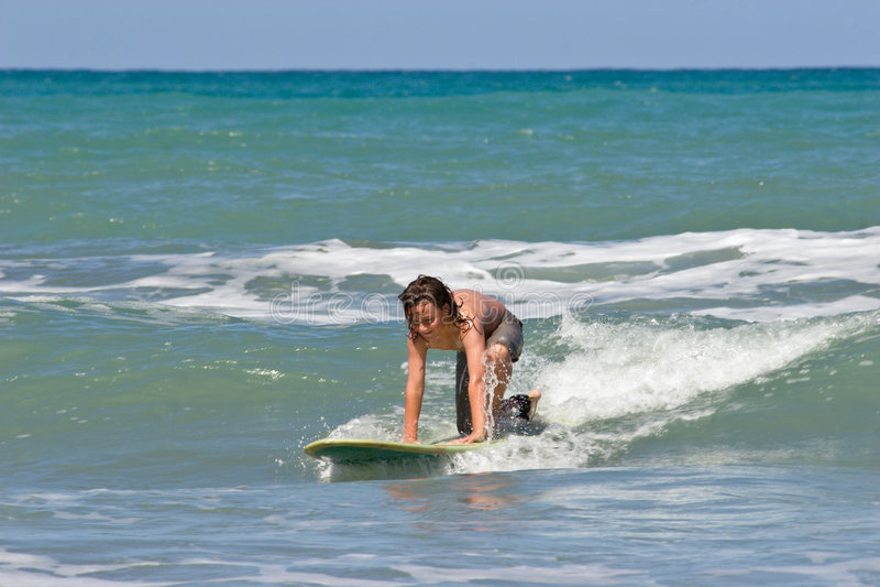 Giovane ragazzo che pratica il surfing nel mare immagine stock