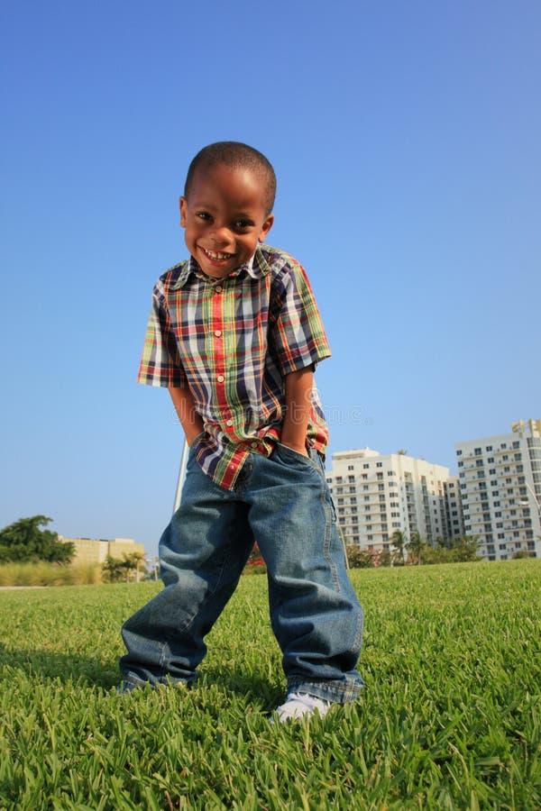 Giovane ragazzo che propone sull'erba immagini stock libere da diritti